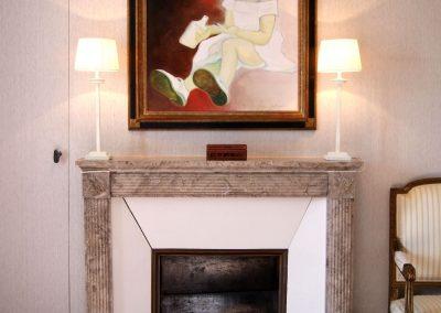 Cheminée, lampes artisanales et portrait