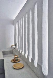 Un claustra stylisé en maçonnerie entre la chambre et la salle de bains.